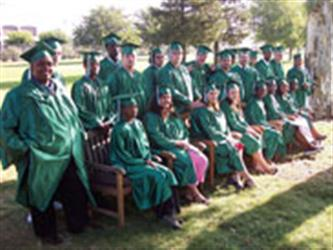 Students sitting on a bench wearing graduation caps and gowns