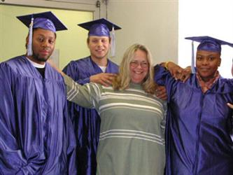 A woman with three graduating students wearing their caps and gowns