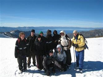 Students on the top of a tall snowy peak overlooking Lake Tahoe